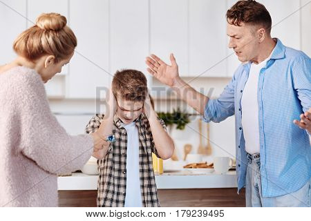 Bad behavior. Serious family couple scolding their son and warning him while standing in the kitchen
