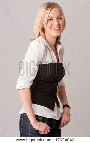 Laughing young blond girl with a shirt and a vest in profile