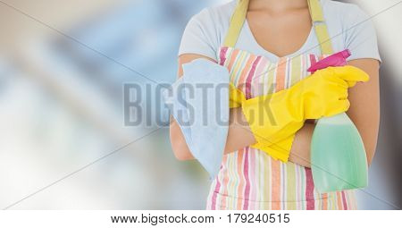 Digital composite of Woman in apron with cleaner against blurry window