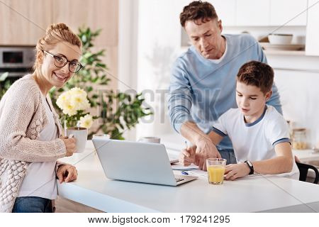 Like my boys. Cheeful mother standing in the kitchen while father helping his son with home work