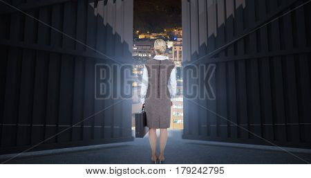 Back turned businesswoman holding a briefcase against glowing modern buildings in city 3d