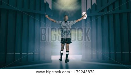 Rear view of athlete with arms raised holding rugby ball against football pitch under bright spotlights 3d
