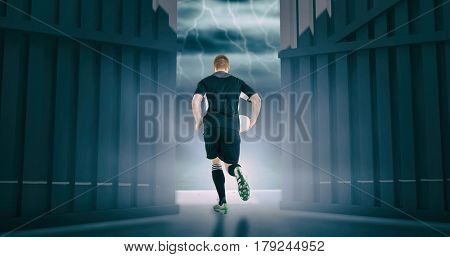 Rugby player running with a rugby ball against football pitch under stormy sky 3d