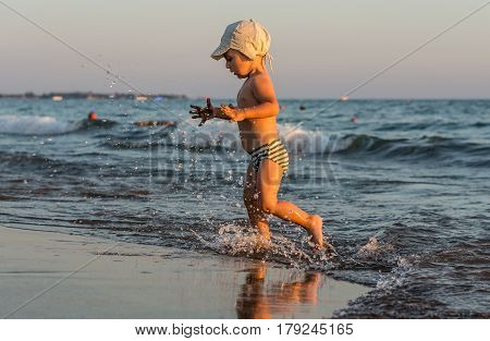 Smiling little baby boy running with splash in the sea on the beach at sunset.