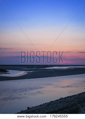 Amazing tropical-like colorful sunset over the Mont Saint Michel area, France