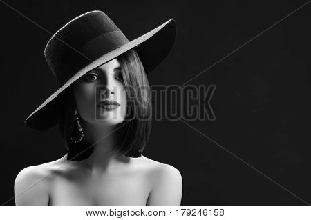 Monochrome studio shot of an elegant young woman posing sensually wearing a wide hat copyspace retro vintage old fashioned stylish beauty makeup red lips brunette sexy seduction concept.