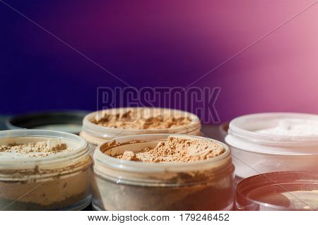 Variety of beauty containers with mineral make-up powder for matt skin on purple and pink background