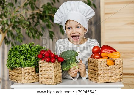 Cute boy in chef uniform with vegetables. Cooking in kitchen at home. Vegetarian. Healthy food