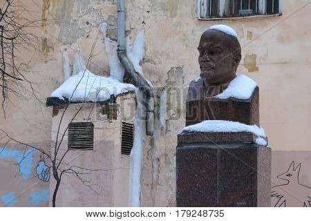 MOSCOW, RUSSIA - FEBRUARY 23, 2016: Lenin's bust covered with snow in the courtyard against the background of the broken wall and waterspout