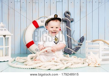Little cheerful boy captain in the maritime interior.