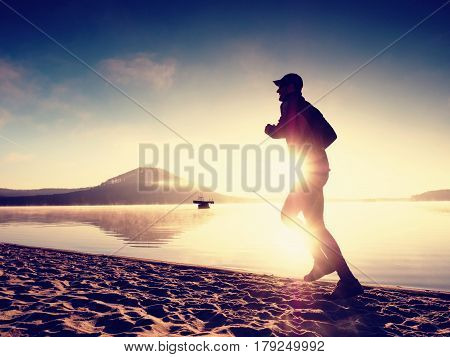 Silhouette Of Sport Active Man Running On The Lake Beach At Sunrise. Healthy Lifestyle.