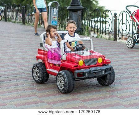 Smiling little brother and sister driving by toy car