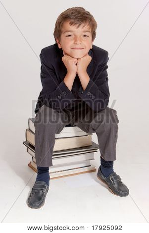 Cute young schoolboy sitting on top of a pile of books