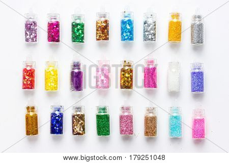 Colorful glitters for nail art and makeup in small glass jars isolated on white background