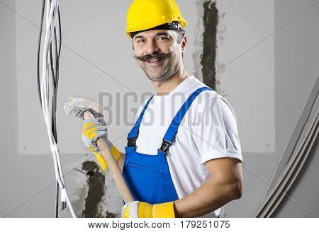 Construction worker holding sledgehammer at a real construction site.