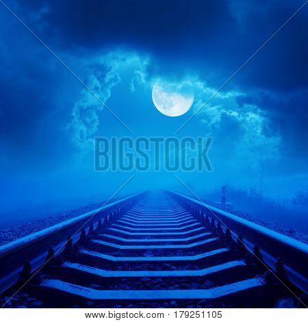 railway to horizon in night with full moon and clouds