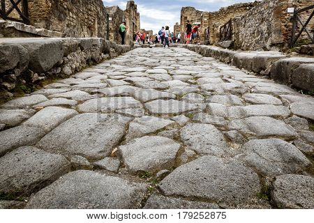 POMPEII, ITALY - MAY 13, 2014: The ancient street. Pompeii is an ancient Roman city died from the eruption of Mount Vesuvius in 79 AD.