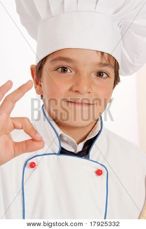 Cute young boy dressed in chef clothes doing and ok sign