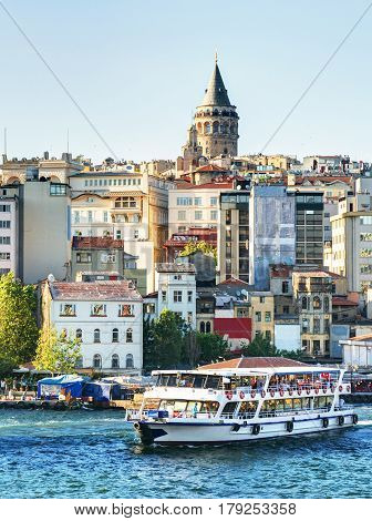 ISTANBUL - MAY 24, 2013: Tourist boat floats past the Galata tower at sunset, Turkey. Golden Horn and the historic Galata area attracts tourists from all over the world.