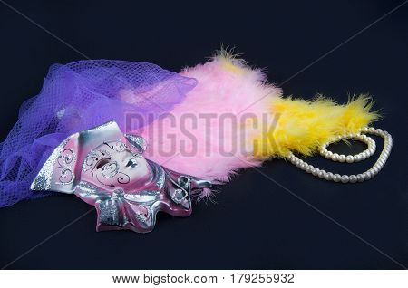 Theater. Porcelain mask pink yellow feathers perl necklace and violet netting lay on black background