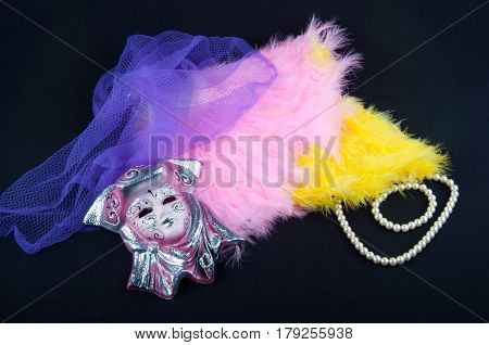 Composition of purple porcelain mask violet netting pink and yellow feathers perl necklace on black background