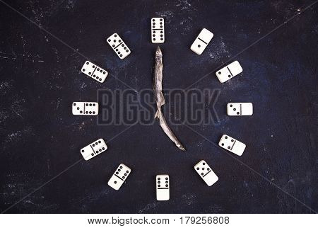 Hours with shooters from fish and figures from dominoes against a dark background. Five hours
