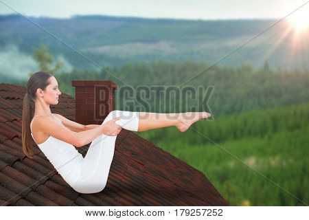 Toned woman doing the boat pose in fitness studio against scenic view of forest