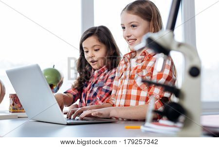 Yet another search. Incredible attentive curious girls using a laptop reading information about human anatomy while attending biology class
