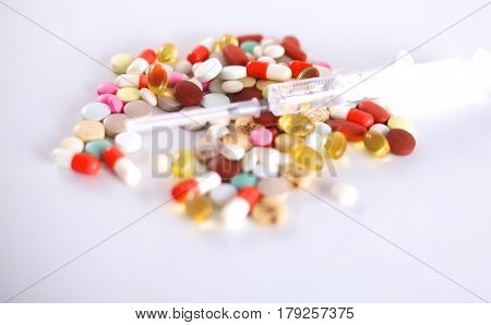 Tablets and a syringe lying on a white table.