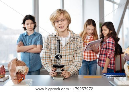 My turn finally. Lively optimistic clever kid posing at the table holding a microscope while his classmates standing in the background