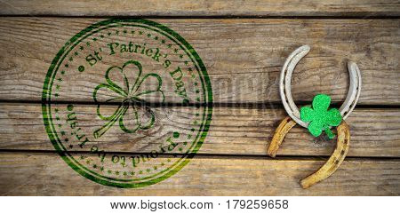 Composite image of St Patrick Day with flower symbol against horse shoe and shamrock