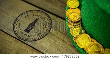 Composite image of St Patrick Day with bottle symbol against st patricks day leprechaun hat with gold chocolate gold coins