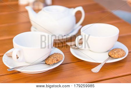 Two white cups and spoons with biscuits teapot on a wooden table