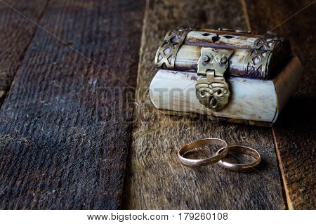 Wedding rings and casket on a wooden table. Black background