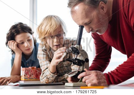 Stunning work, guys. Charming engaged energetic man monitoring his students scientific work concerning bacteria while using a microscope
