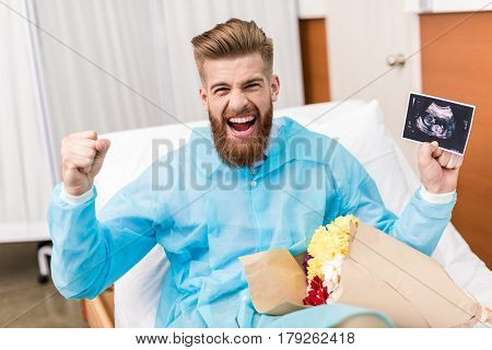 Front View Of Happy Young Man With Flowers And Sonogram In Hospital