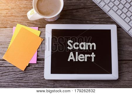 Tablet Pc With Scam Alert And A Cup Of Coffee On Wooden Background.
