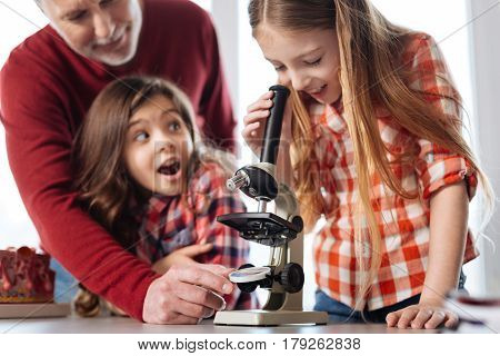Do you see that too. Cute engaged smart girl expressing her admiration while exploring a microscopic world using special tool