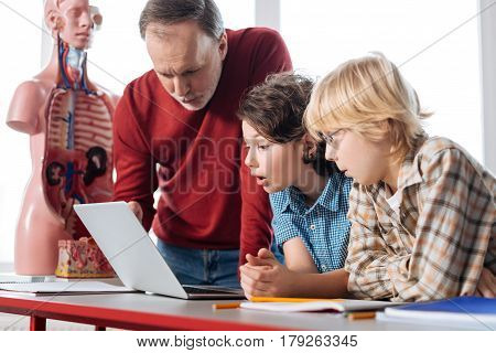 Can you have a look. Talented admirable productive kids asking the professor for advice after completing an experiment and analyzing the obtained data
