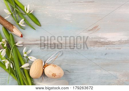 Traditional easter background. Easter eggs and snowdrop flower on blue wooden background top view.