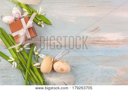 Traditonial easter background. Easter eggs and snowdrop flower on blue wooden background top view.