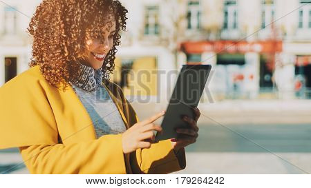 Attractive smiling curly Brazilian woman in yellow coat having video call using digital tablet adult cute lady making selfie on touch pad with copy space for your message or promotional content