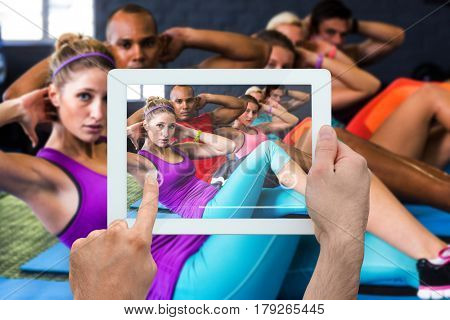 Hand holding tablet pc against portrait of friends with hands behind back while stretching