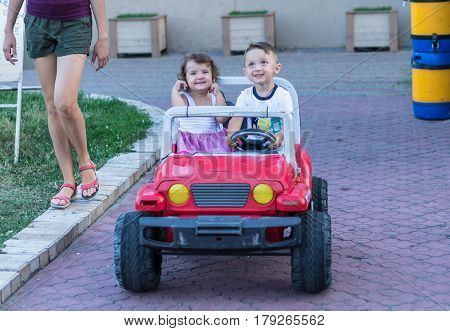 Smiling little brother and sister driving by toy car. Portrait of happy little kids on the street. Funny cute children making vacations and enjoying summer. Healthy lifestyle. Positive human emotions.