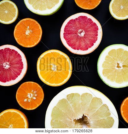 Lemon, orange, mandarin, grapefruit and sweetie on black background. Flat lay, top view. Fruit background