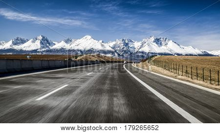 Car on highway D1 and snowy peaks of High Tatras mountains Slovakia