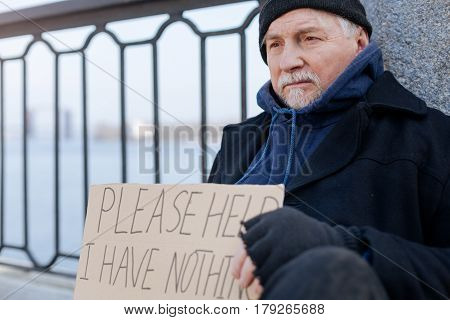 Have no idea. Frustrated homeless person wrinkling his forehead wearing warm clothes looking aside