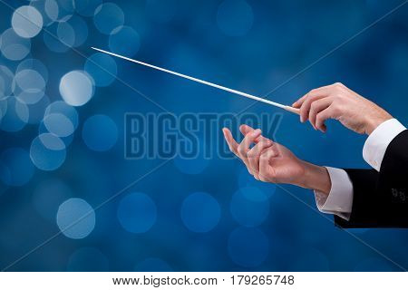 Male orchestra conductor hands with gesture one with baton. Leadership and manager concepts.