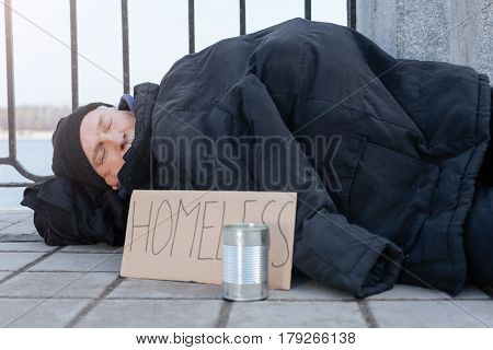 Do not ignore. Elderly male person sleeping outdoors covering himself with jacket, keeping tin for money on the foreground