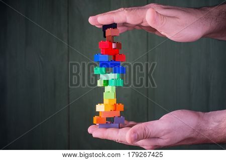 Human hand holding abstract construction from colorful plastic stack blocks. The concept of logical thinking.